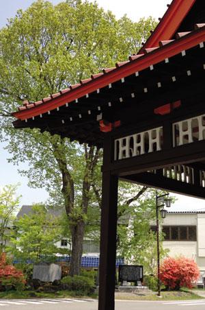 正面入口の欄間にあしらわれた法政大学のイニシャル「H」。駅前広場には「北軽井沢開発の碑」などが見える。