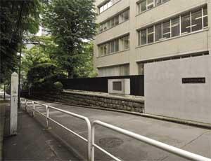 富士見坂の上から見た80年館裏門と碑(中央石垣の上)。